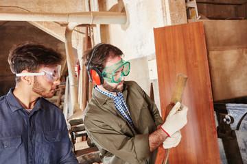 Handwerker messen zusammen Holz