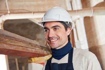 Mann als Bauarbeiter mit Holz