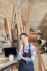 Frau mit Mobiltelefon in Schreinerei