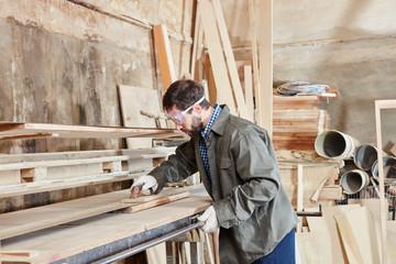 Schreiner schleift Holz an Schleifmaschine
