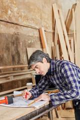 Handwerker arbeitet an einer Zeichnung