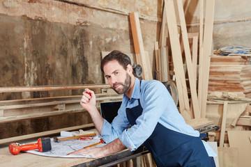 Handwerker arbeitet an einem Bauplan