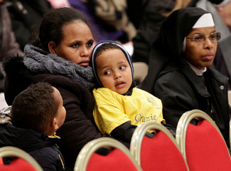 Migrants wait for Pope Francis to lead a special mass to mark International Migrants Day in Saint Peter's Basilica at the Vatican