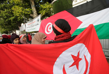 A woman carries a Tunisian flag during demonstrations on the seventh anniversary of the toppling of president Zine El-Abidine Ben Ali, in Tunis
