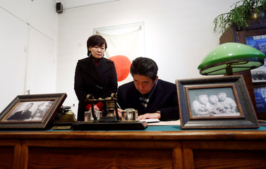Japan's Prime Minister Shinzo Abe signs a guest book as he visits a former home of Chiune Sugihara, a Jew-saving Japanese diplomat in Kaunas