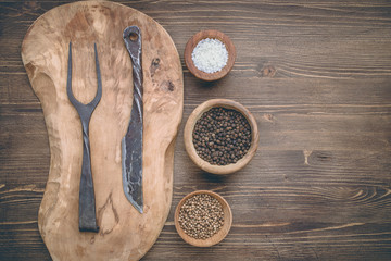 Cutting board with vintage meat fork and knife and seasonings on wooden background, top view