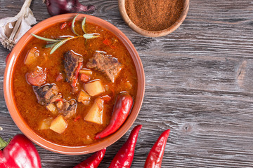 Goulash on rustic wooden  background. Traditional hungarian meal,  beef stew. Copy space