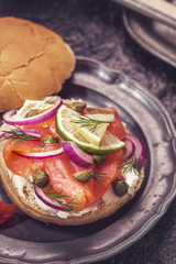 Burger with smoked salmon and cream cheese on vintage plate, close-up