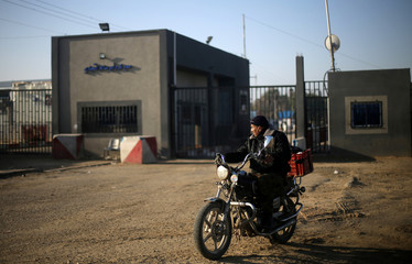 Palestinian rides a motorcycle outside Kerem Shalom, the main passage point for goods entering Gaza, after it was shut down by Israel, in the southern Gaza Strip
