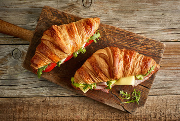 two croissant sandwiches on wooden table
