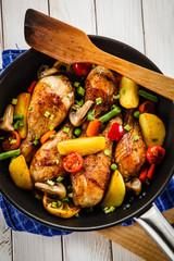 Grilled chicken drumsticks with vegetables on wooden background