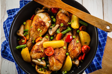 Grilled chicken drumsticks with vegetables on wooden background