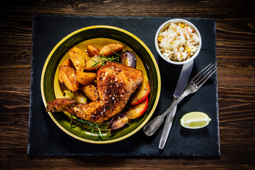 Roast chicken leg with chips on wooden background