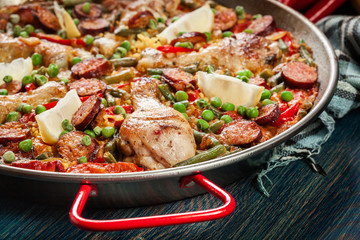 Traditional paella with chicken legs, sausage chorizo and vegetables served in paellera