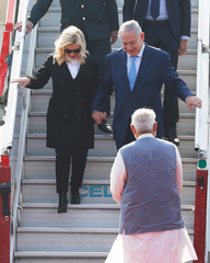 Israeli Prime Minister Benjamin Netanyahu and his wife Sara disembark from a plane as India's Prime Minister Narendra Modi watches upon their arrival at Air Force Station Palam in New Delhi