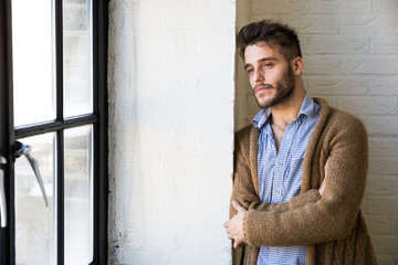 Handsome young dreamy man standing at window and looking away.