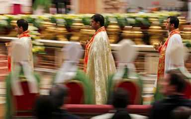 Priests walk as Pope Francis leads a special mass to mark International Migrants Day in Saint Peter's Basilica at the Vatican