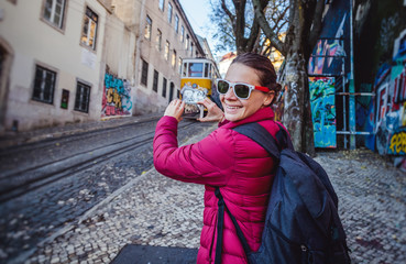 beautiful young woman tourist in lisbon doing photo on mobile phone. Travel, vacation, technology, Portugal is a popular destination for traveling in Europe