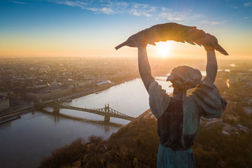 Budapest, Hungary - Aerial sunrise at the Statue of Liberty with Liberty Bridge and River Danube at background taken from Gellert Hill