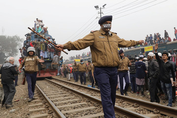 """Security personnel clear the rail track as an overcrowded train leaves Tongi rail station after the final prayer of """"Bishwa Ijtema"""", on the banks of the Turag river in Tongi near Dhaka"""