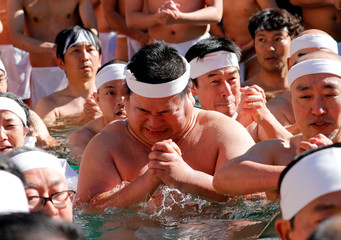 People wearing loin cloths pray as they bathe in ice-cold water in a ceremony to purify their souls and wish for good health in the new year at the Teppozu Inari shrine in Tokyo