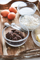 Baking ingredients for chocolate cake muffins or cookies lying ready on wooden kitchen tray. Mise en place, white background, measured ingredients.