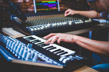 male musician playing midi keyboard synthesizer in recording studio, focus on hands