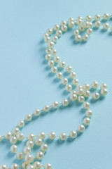 White pearls on blue background - luxury fashion concept