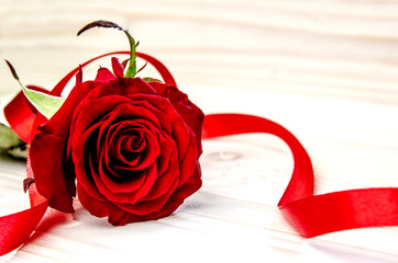 Red rose, wrapped in red ribbon on a white wooden surface.