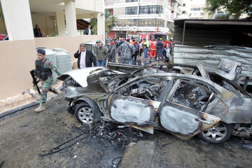 Lebanese soldiers are seen inspecting a damaged car in Sidon