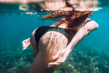 Attractive young woman swimming in ocean, underwater photo
