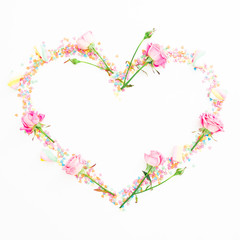 Valentine's day composition. Heart made of pink flowers and candy confetti on white background. Flat lay, Top view.
