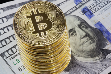 Metal bitcoin coins on one hundred dollar bills background.