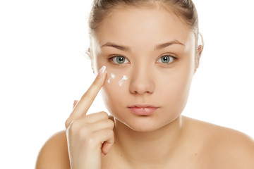 young girl applying face cream on white background