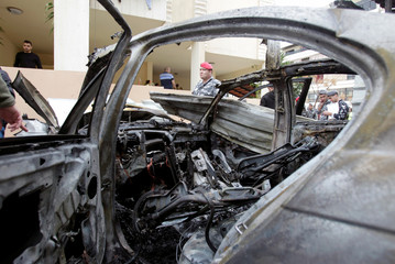 Lebanese policemen are seen next to a damaged car in Sidon