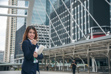 Portraits of beautiful asian woman look cheerful and confidence is standing and feeling success with work while holding folder document.