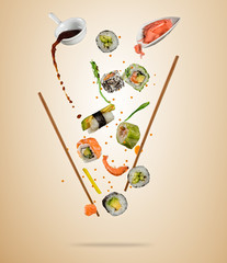 Flying pieces of sushi with wooden chopsticks, separated on beige background