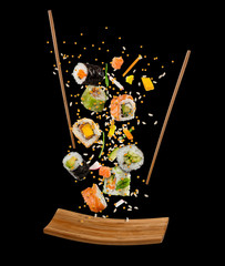 Flying pieces of sushi with wooden chopsticks and plate, isolated on black background.
