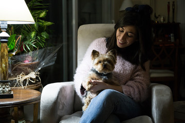 Cheerful young woman sitting with cute little dog in armchair and smiling.