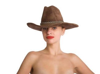 portrait of a young slender girl with bare shoulders looking thoughtfully at a cowboy hat on her head