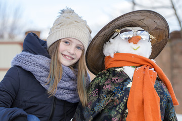 Happy young girl with a snowman, close up