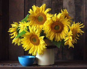 Bouquet of sunflowers in a can on the table.