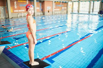 Cute schoolgirl in swimsuit, swim-cap and goggles looking at camera while standing on diving board