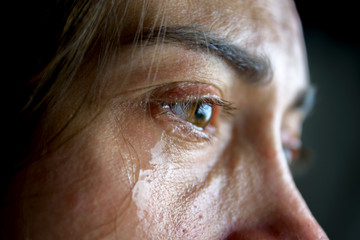 The woman is crying. Close-up eyes and tears.