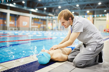 Young man or trainer of swimming giving first aid to one of his learners after accident
