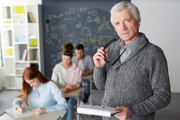 Mature teacher with eyeglasses and notepad looking at camera with students writing test on background