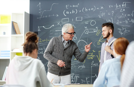 Strict grey-haired teacher pointing at one of students while talking to him by blackboard
