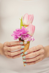woman hands holding spring flowers in an ice cream cone, sensual studio shot can be used as background