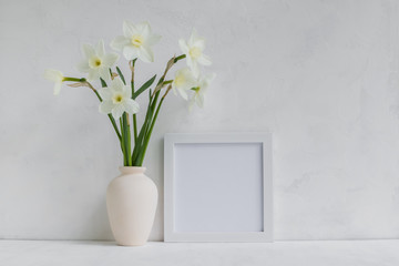 Mockup with a white frame and white daffodils in a vase