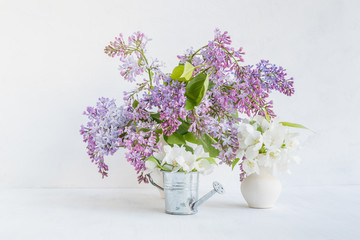 Bouquet of lilac in a vase on a light background